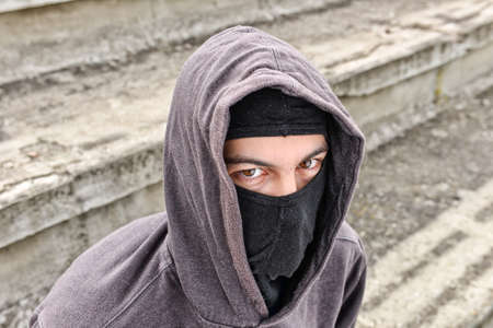 thievery: unrecognizable young man wearing black balaclava sitting on old stairs, looking at the camera