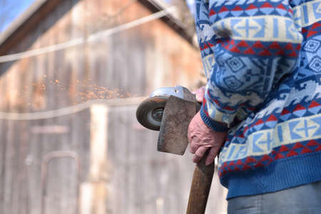 burnish: Close up of a man sharpen an ax using electric grinder. Sparks while grinding iron. Selective focus