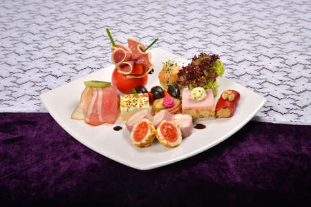 carnes y verduras: Antipasto y restauración plato con diferentes aperitivos (frutas, verduras, carnes, quesos) sobre fondo blanco y morado