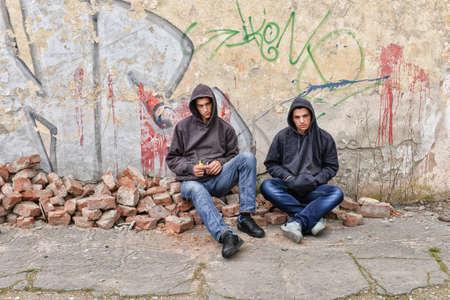 raperos: dos gamberros callejeros o los raperos de pie contra una pared de graffiti pintado se están preparando para fumar un cigarrillo