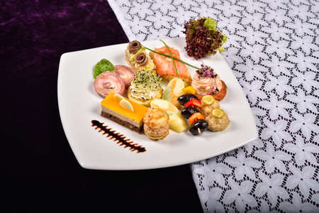 Antipasto and catering platter with different appetizers(fruits, vegetables, meats, cheeses)on white and purple background