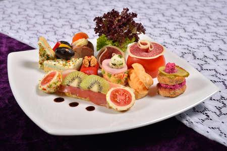 carnes y verduras: Antipasto y restauraci�n plato con diferentes aperitivos (frutas, verduras, carnes, quesos), men� del restaurante Foto de archivo