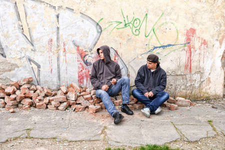 raperos: two street hooligans or rappers standing against a graffiti painted wall are preparing to smoke a cigarette