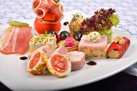 carnes y verduras: Cierre de antipasto y restauración plato con diferentes aperitivos (frutas, verduras, carnes, quesos) sobre fondo blanco y morado Foto de archivo