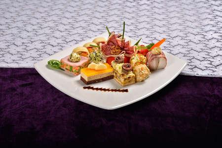 carnes y verduras: Antipasto y restauraci�n plato con diferentes aperitivos (frutas, verduras, carnes, quesos) sobre fondo blanco y morado