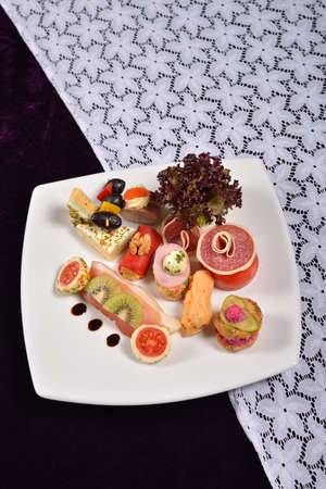 appetizers menu: Antipasto and catering platter with different appetizers (fruits, vegetables, meats, cheeses), restaurant menu