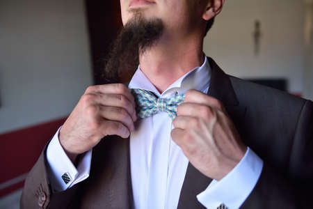 formal dressing: Mid section of happy groom adjusting his bow tie