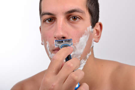 shaving cream: Handsome young man with lots of shaving cream on his face preparing to shave with razor