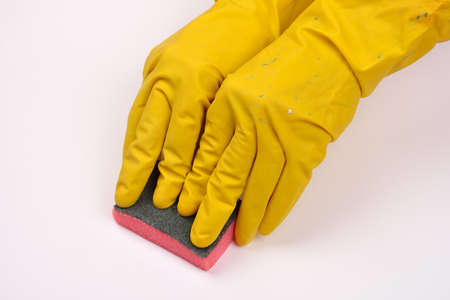 women protecting hand with rubber glove from detergents as they use a cleaning sponge  on white background 写真素材