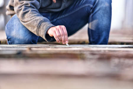 extinguishing: Hand of a young man extinguishing cigarette on a old bridge. Concept quit smoking. Selective focus Stock Photo