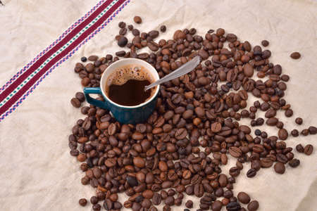 pleasures: Roasted coffee beans with cup and spoon on jute background. Morning pleasures