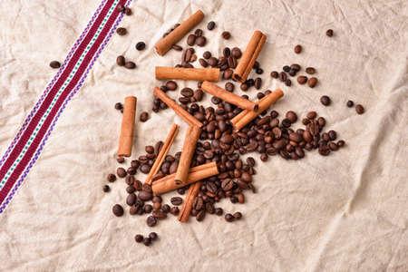 pleasures: Coffee beans with cinnamon sticks on vintage texture. Roasted coffee beans on jute background. Morning pleasures. Awakening flavors. Selective focus