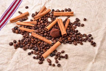 pleasures: Coffee beans, cinnamon sticks and truffles on vintage texture, jute background. Morning pleasures. Awakening flavors. Selective focus Stock Photo
