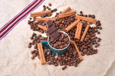 pleasures: Cup of coffee with cinnamon sticks, bitten bar of chocolate on vintage texture. Roasted coffee beans on jute background. Morning pleasures. Selective focus Stock Photo