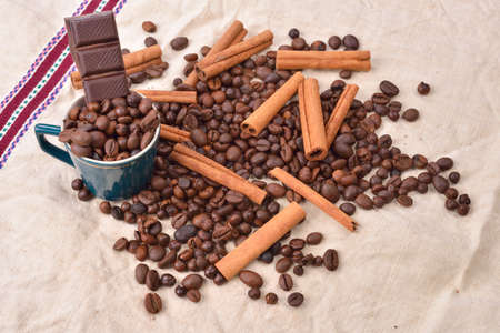 pleasures: Cup of coffee with cinnamon sticks, bar of chocolate on vintage texture. Roasted coffee beans on jute background. Morning pleasures. Selective focus
