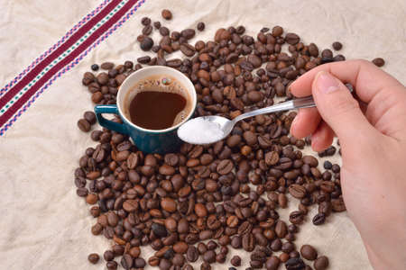 pleasures: Hand of a woman mixing the sugar in a green cup of coffee. Roasted coffee beans on jute background. Aid waking in the morning. Morning pleasures