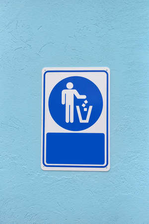 conservative: Recycled symbol over blue and white background on a wall. Man throwing trash into dust bin. Keep clean