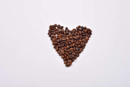Roasted coffee beans in the shape of the heart. Concept of loving coffee. Morning awakening