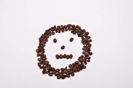 CLOSE UP FACE: Picture shape face made of coffee beans on white background. Morning pleasure