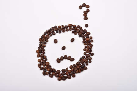 CLOSE UP FACE: Picture of a sad face with question mark made of coffee beans on white background. Morning pleasure Stock Photo