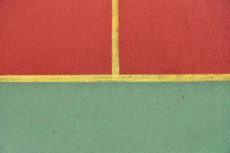 granule: Detail of crossed yellow lines on football playground. Detail of lines in a soccer field made from red and green granule rubber Stock Photo