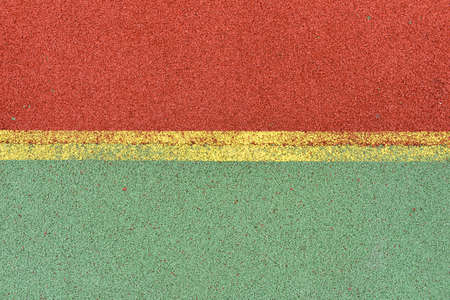 granule: Detail of yellow lines on football playground. Detail of lines in a soccer field made from red and green granule rubber