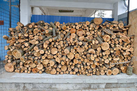 staging: raw debarked wood logs in a lumber staging and storage yard. Raw timber stacked and ready to used in a car wash