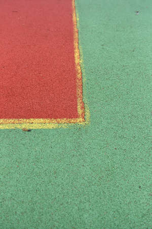 erased: tennis court rubber play game background texture pattern with erased yellow line. Old and untidy land. Green and red background Stock Photo