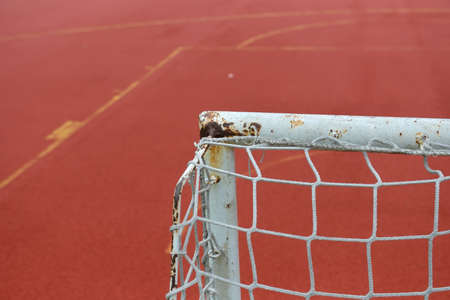 granule: Detail of old and rusty gate of mini football at a soccer field made from red and green granule rubber. Stock Photo