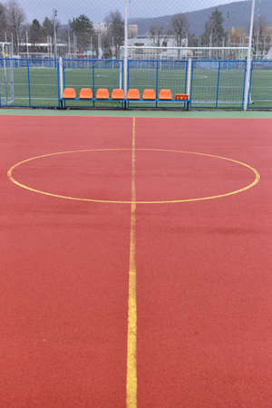 granule: Soccer field made from red granule rubber. Football field background. Center of playground. Red chairs behind. Selective focus