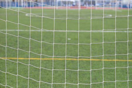 soccer net: Close up detail of a soccer net against green grass on a cloudy day. Selective focus