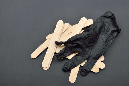 Black glove and wooden spatulas for wax on black. Preparing for epilation Stock Photo