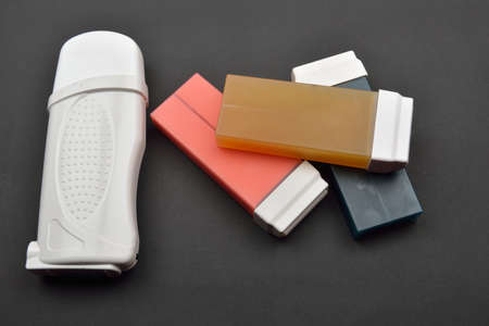 wrest: Picture of different types of liposoluble wax cartridges for waxing and white wax warming device on black background