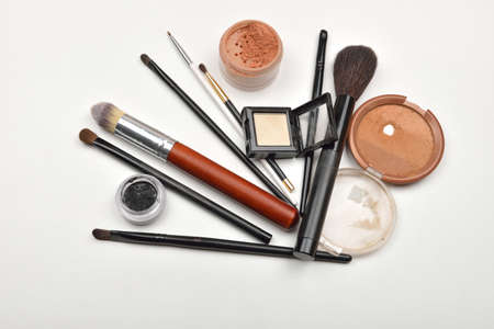 Close-up of open jar of loose powder, compact powder, eyeliner, eyebrow powder, eyeshadow makeup brushes and on white