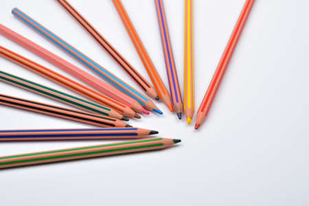 close up picture of colored pencil crayons with stripes on white