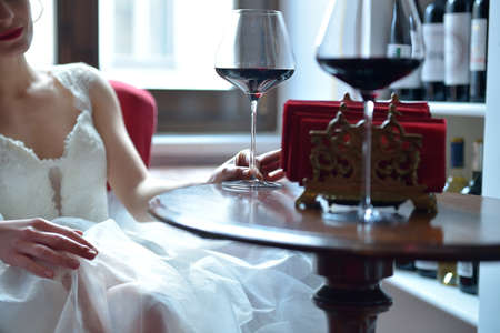 Beautiful young bride in a white dress sits at a wooden table with a glass of red wine. Celebration, wedding reception in the restaurant. Selective focus. Stockfoto