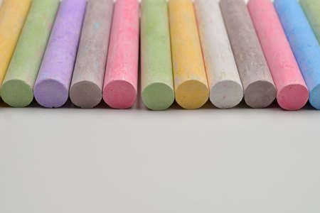 Pieces of chalks in a variety of colors arranged in line on a white background. Back to school,education, arts, creative. Image with room for text