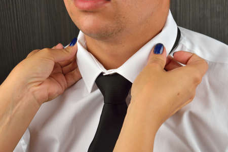 get dressed: Womans hands adjusting black tie and the neck of the shirt. Wife helping his husband to get dressed. Clothes detail. Lights and shadows