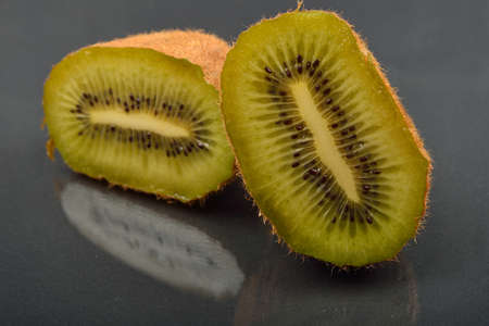 Close up of a kiwi cut in two with wizened skin on dark reflection background. Natural organic vegetarian food. Healthy snack Stock Photo