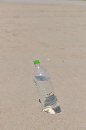 unlabelled: Ice cold unlabelled bottle of refreshing water standing upright in the golden sand on a tropical beach under the hot rays of the summer sun. Water requirements, heat