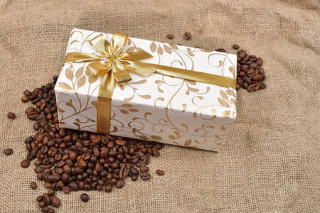 Beautiful gift box in roasted coffee beans on a brown jute background. Selective macro focus. Copy space Stock Photo