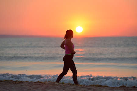 Silhouette of a young girl running alone along the beach of the sea during an amazing sunrise. Concept of sport and freedom. Healthy training