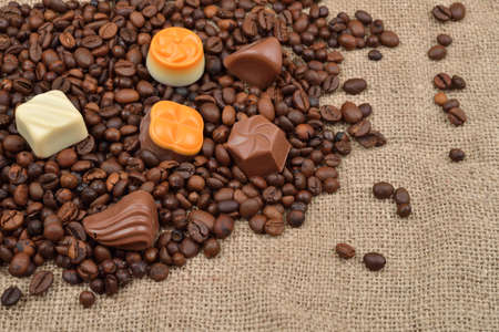 Jute background. Assortment of dark, white and milk chocolate stack on roasted  coffee beans. Sweet and rustic image. Selective macro focus. Chocolates background. Sweets Stock Photo