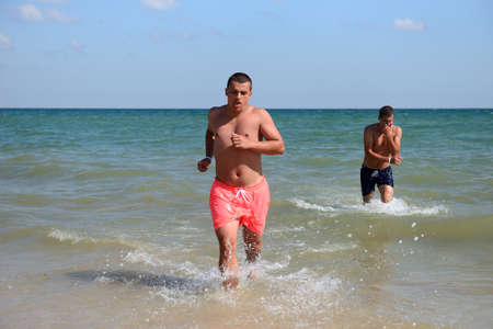 Two friends in the water, enjoying the sun and relaxation one of them is running from the water of the Black Sea. Cold water, burning sun