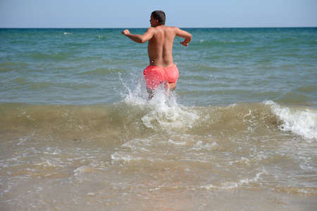 Young man is running in the water of the Black Sea, ready to have some fun in his vacation, enjoying the sun and relaxation. Jumping for joy, cold water, burning sun