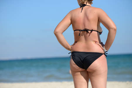 Overweight young woman in swimsuit near the sea, looking at the water, enjoys the hot sun in his summer holiday Stock Photo