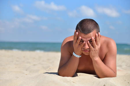 Handsome young man with the head in his hands, lying to sunbath on the sand. Summer travel holiday at the sea