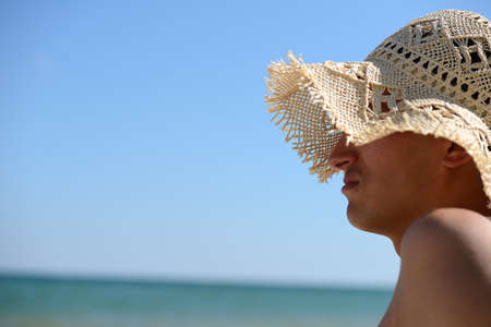 Funny picture of a relaxed young man with straw hat for woman stands to sunbath on the beach. Summer vacation. Sea in the background