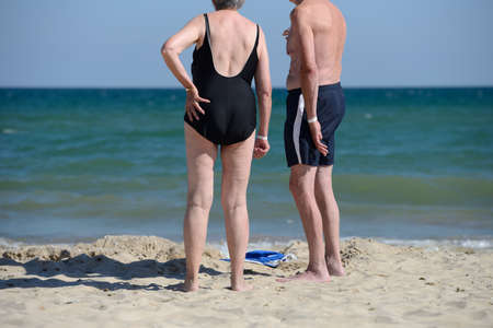 Senior couple at the beach on a sunny day. Mature couple in love looking at the seaside,walking barefoot on the sand