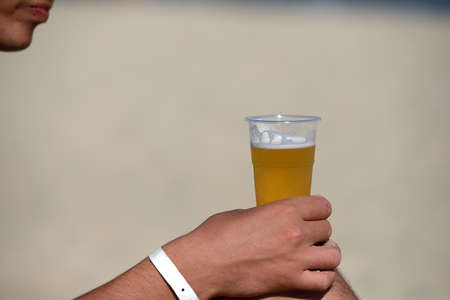 Closeup of the hand of a man with a refreshing beer on the beach near the sea. Resort relaxation. Summer holiday. Burning sun Stock Photo